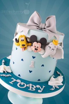 This Terrific Mickey, Pluto, and Dumbo 1st Birthday Cake was made by Little Cherry Cake Company. This Disney cake is in the form of a hatbox. Mickey Mouse, Pluto, and Dumbo are peering out of the hatbox. The hatbox cake is light blue with small dark blue Mickey heads all...