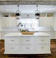 Elegant white kitchen with rustic beam, lanterns, marble, and design by M Naeve. White Kitchen Island, White Kitchen Cabinets, Kitchen Time, New Kitchen, French Farmhouse Decor, French Country, House Essentials, Cocinas Kitchen, Kitchen Wall Colors