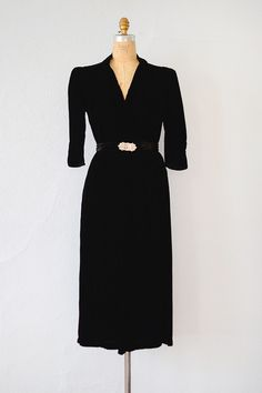 1930s black silk velvet semi formal party dress has v-neckline with lovely knot detail (see the last photo, I have lightened it considerably so detail is visible) Has matching belt with pretty art deco rhinestone encrusted buckle. Sleeves are about 3/4 length.
