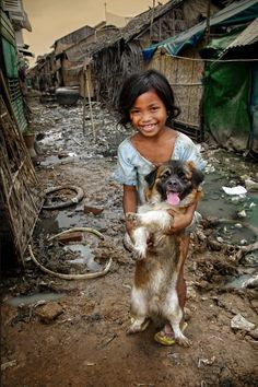CHILDREN ARE SO RESILIENT. Despite of how poorly this child lives, something as simple as friendly dog can bring a smile to her face.
