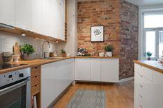 biała kuchnia ze ścianą z czerwonej cegły i deskami z drewna na podłodze - Lovingit.pl