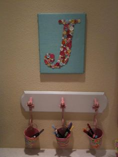 Hang pretty buckets from a small coat rack for the items you reach for most. And the button initial