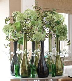 """Ken Marten, """"With branches of apple and hydrangeas in place, the vases became tree trunks, the apple and hydrangea became the canopy and the Eucharis the underplanting, to create a fresh-looking woodland scene in green and white."""""""