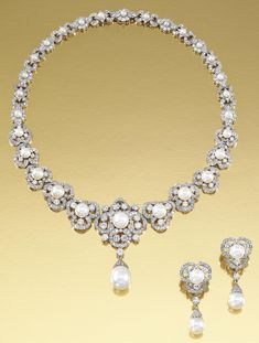 CULTURED PEARL AND DIAMOND DEMI-PARURE.  The necklace designed as a series of graduated clusters, each centring on a cultured pearl within stylised floral surrounds of brilliant-cut diamonds, supporting at the front a cultured pearl drop dressed by a diamond-set cap, together with a pair of ear pendants of similar design, necklace length approximately 395mm, cultured pearl drop detachable, pair of ear pendants with clip and post fittings, cultured pearl drops detachable, fitted case.