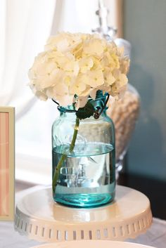 THE CENTERPIECE Fill glass mason jars with white flowers such as hydrangea from your back yard or grocery store  and place in a row down the center of your table.