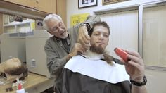 Lance Anderson has Erich hold a tiny fan to blow fumes away from his face during beard removal.