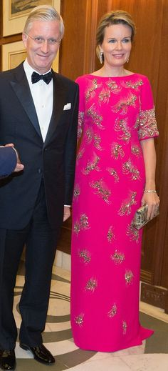 Belgium's King Philippe, sweltered in the 29-degree heat in a dark tuxedo suit while Queen Mathilde, managed to keep her cool in a bejewelled hot pink dress. The modest floor-length gown that skimmed the figure was perfect for the colourful occasion. She added a miniature clutch bag decorated in a similar pattern to her dress, and added glamour with over-sized diamond drop earrings. Her blonde tresses were pulled back into a loose bun at the nape of her neck.