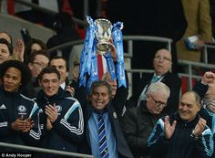 The Chelsea boss finally gets his hands on the trophy and lifts it aloft to the acclaim of...