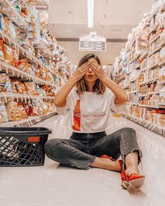 Emily Vartanian st… Emily Vartanian styles a Coca-Cola graphic tee with black denim and red heels as she poses for a photoshoot in a grocery store
