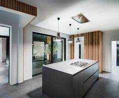 Minimal SieMatic handleless island in dark grey laminate.  Flush ceiling extractor and 12mm worktops to create a sleek contemporary feel