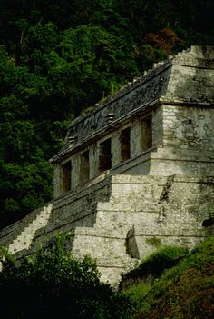 The Mayan Temple of the Inscriptions pyramid ruin emerges from the rainforest at Palenque in Chiapas, Mexico.