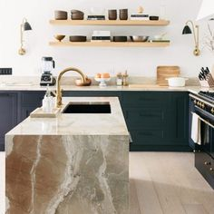 You have to see these dark blue kitchen cabinets with marble counters and natural wood accents. Love it! #KitchenDesign #HomeDecorIdeas @istandarddesign