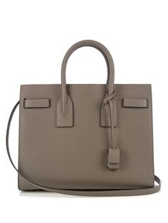 Saint Laurent's Sac De Jour tote is timelessly elegant. This small style is expertly crafted in Italy from grained leather in a versatile taupe-grey hue, and finished with expandable accordion side panels to create extra space in the two internal compartments. Attach the shoulder strap when dashing between meetings.