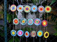 Upcycled CDs w colorful #crochet mandalas over them and then are hung in strings. By Cristina Vasconcellos.