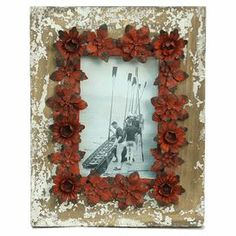 """Picture frame with a floral border.   Product: Picture frameConstruction Material: Wood, glass and metalColor: Beige and rustFeatures:  Distressed finishRustic floral embellishmentHolds one photo Dimensions: 10"""" H x 7.75"""" W"""
