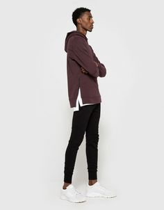 From John Elliott, a hooded sweatshirt in Maroon. Featuring flatlock seams, long sleeves with ribbed cuffs, interior kangaroo style pouch pocket, straight back yoke, French terry lining, stepped hem with partial side seam zippers and a slim fit.  • Hood