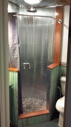 Neo-angle shower with corrugated tin walls with river rock stone floor.