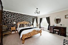 gold bed and black wallpaper