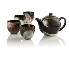 """This Japanese stoneware set has a unique reactive glaze which changes on each set once the heat of the kiln comes into contact with the pieces. Each set will have varying amounts of red. The name means """"smoke"""" as it evokes the plumes of smoke wafting up from a fire. Each set includes one 14oz (410mL) teapot and four 5oz(145mL) tea cups. Made in Japan. Teavana Exclusive. Hand wash only."""
