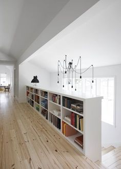 """Flournoy's favorite aspect of the design is that """"every space in the house is used and appreciated."""" This light-filled hallway overlooking the staircase connects the home's two bedrooms to an upstairs living space, and provides the ideal spot for another bookcase. Flournoy and his partner found the hall chandelier, along with the salvaged mill table that they repurposed as their kitchen island, on a trip to Chicago."""