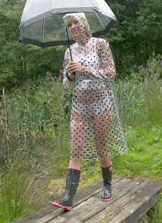 Only light white garment with invisible colored pantyhose under transparent polka doted transparent pvc raincoat.