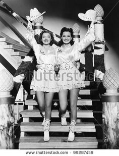 stock photo : Two young women stepping down a staircase waving their western hats