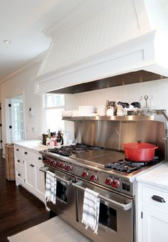 Wow look at this Wolf range and white range hood.