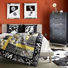 2 graphic pillows and 2 graphic pieces of wall art mirror one another and = focal point. burnt orange wall color brings earthy tone