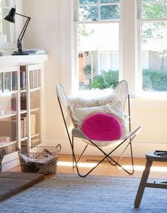 Black steel Butterfly chair with white canvas cover, sheepskin and pink pillow