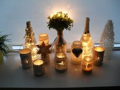 Lege flessen/potten/blikken!  Alles gespoten in silver/wit, flessen gevuld met lampjes, rest met waxinelichtjes. Met spijker gaatjes in de blikken gemaakt.