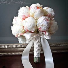 This ivory peony wedding bouquet is romantic and elegant. Fifteen natural ivory peony buds are hand-tied with ivory satin ribbon, braided and bowed. Each peony has soft pink accents for a fresh and na