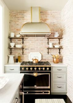 Rustic kitchen with golden accents, black stove and oven, and white decorative bowls/cups