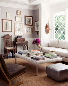 Windsor Smith asymmetrical room. Moroccan side chair. Biscuit tufted ottoman. Contemporary sofa. Silver square ottoman. Brown leather chair with brass frame. Antique pencil sketches. Gold frames.