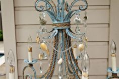 Fantastic wrought iron chandelier!!    Re purposed wrought iron chandelier (new) painted in a robins egg blue, featuring seashells, rope twine, and