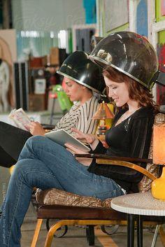 Young women sitting in hood hair dryer by Andersen Ross ...