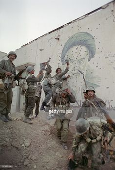 Iraqi soldiers pose 20 April 1988 in front of a huge bullet-pocked mural of Iranian leader Ayatollah Khomeiny in the strategic Faw peninsula of southeast Iraq that was partly occupied by Iranian.