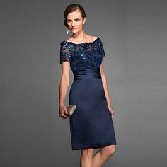 Modelo veste vestido curto ombro a ombro de renda azul marinho com clutch dourada de mao.