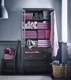 Chic and modern bathroom design in a purple, pink and gray color scheme. 50 shades of gray feature in this bathroom with wainscoting, chair and cabinets painted a darker shade of gray and the walls in a slightly lighter shade. The wow factor comes in with the towel arrangement with  folded, and rolled towels in…