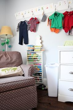 Hooks on wall over changing table to hold clean clothes to be used during the week.  From Living With Kids: Shannon Molenaar