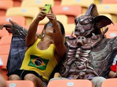 A fan takes a selfie with a man wearing a costume (© Mast Ihram/EPA)