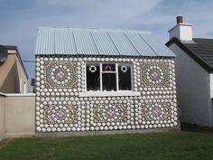 She sticks sea shells on her house wall