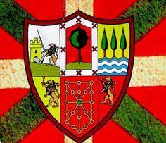 """ESCUDO DE ARMAS DE EUSKAL HERRIA - Fue diseñado por Jean Jaugain para las """"Congrès et Fêtes de la Tradition Basque"""" que se celebraron en San Juan de Luz en 1897 bajo el lema """"Zazpiak Bat"""" (Las Siete son Una) ideado por D'Abbadie. Es el símbolo de todo el País Vasco y aceptado por la población. En el diseño original los escudos aparecen en el siguiente orden: Navarra (Navarra y Baja Navarra), Guipúzcoa, Vizcaya, Álava, Labourd y Soule. Anteriormente, en las """"Fêtes"""" celebradas en 1892, se…"""