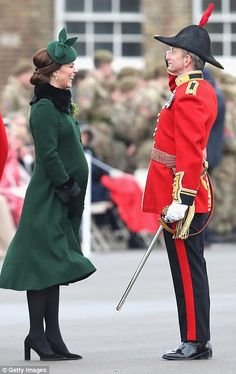 The Duchess is pictured giggling as she is saluted by a member of the Irish Guard...