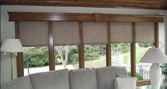 Wood cornice compliments the wood molding and completes the look of these beautiful roller shades. Available from Budget Blinds.