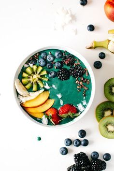 Turquoise green smoothie bowl with blackberry, blueberry, peach and strawberries