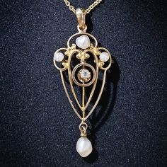 This darling original Art Nouveau lavalier necklace, from the early 1900s, twinkles in the center with a single European-cut diamond and the graceful open work pendant shimmers with four freshwater pearls. The pendant, minus the loop, measures 1 1/8 inches, the new chain measures 16 inches.