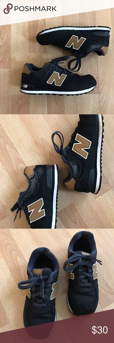 574 New Balances Black new balances with hints of tan and blue. Photos show areas of wear. Shoe is pre-loved but is still in great condition! :) Size 5.5 in kids but fits like a 7 in women's! New Balance Shoes Sneakers
