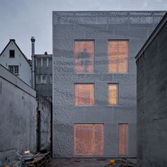 Chris Kabel has wrapped this house and studio in Amsterdam with a perforated facade that catches the light like a hanging sheet of fabric.