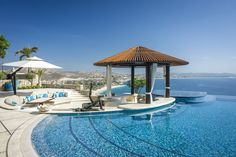 A Cabo home has a pool with a firepit island, multiple hot tubs and built-in tables.