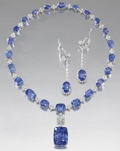 SAPPHIRE AND DIAMOND NECKLACE AND PAIR OF EAR PENDANTS.  The necklace designed as a line of graduated cushion-shaped sapphires interspersed with brilliant-cut diamond clusters, decorated at the front with a detachable pendant of similar design; the pendent earrings each composed of a foliate surmount set with marquise-shaped and brilliant-cut diamonds, suspending a detachable pendant set with an oval sapphire, brilliant-cut and baguette diamonds